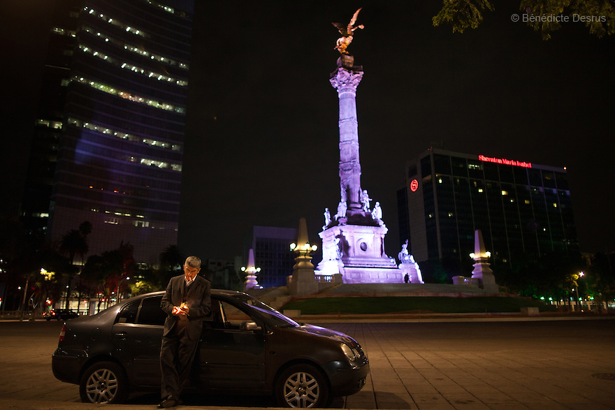 """Donovan parked at Mexico City's iconic Angel of Independence monument, smoking and listening to his favorite AM radio station in Mexico City on May 25, 2015. Some nights he will spend up to an hour there, peacefully watching over the empty streets. Donovan Tavera, 43, is the director of """"Limpieza Forense México"""", the country's first and so far the only government-accredited forensic cleaning company. Since 2000, Tavera, a self-taught forensic technician, and his family have offered services to clean up homicides, unattended death, suicides, the homes of compulsive hoarders and houses destroyed by fire or flooding. Despite rising violence that has left 70,000 people dead and 23,000 disappeared since 2006, Mexico has only one certified forensic cleaner. As a consequence, the biological hazards associated with crime scenes are going unchecked all around the country. Photo by Bénédicte Desrus"""