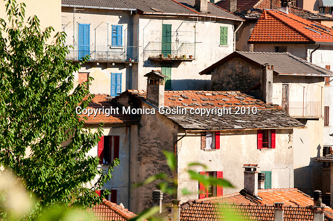 Stone houses with colorful shudders in Nesso, a small town on Lake Como, Italy