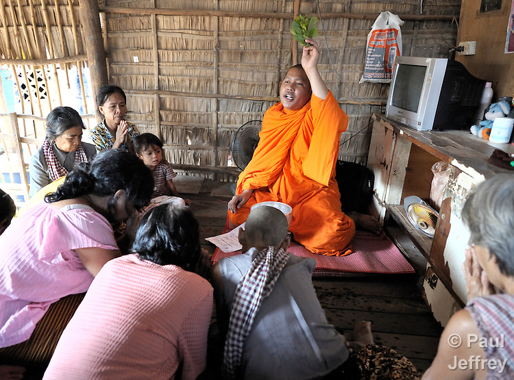 Buddhist monk Han Kimsoy sprinkles water on members of a self-help women's group in the Phnom Penh neighborhood of Sen Rikreay. He is one of several monks who work with the Salvation Centre Cambodia in teaching meditation techniques to people living with the HIV and AIDS. Many of the women in the group are infected or affected by the virus.