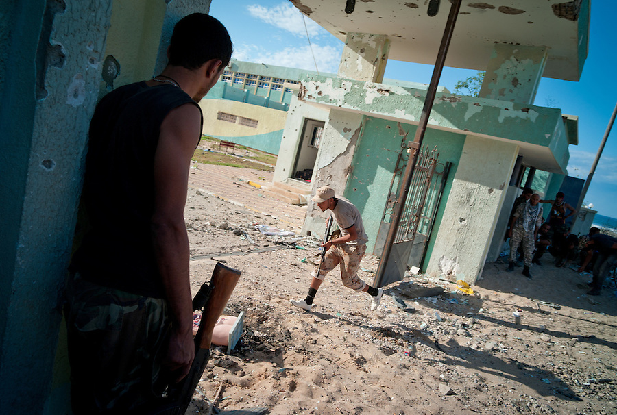Anti-Gaddafi fighter runs to engage a Gaddafi loyalist position in Sirte, Libya.