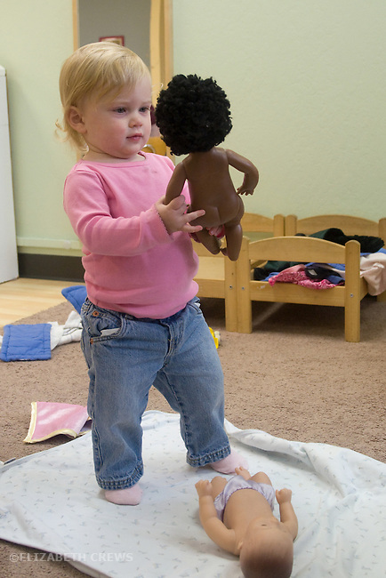 Berkeley CA Girl, one and a half, interacting with black doll while playing at Children's Creative Play Space MR