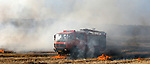 A fire truck is seen driving through plumes of smoke on its way to put out a fire in a field on the outskirts of the town of Afula, April 25th, 2009. Photo by : Michael Salman / JINI..