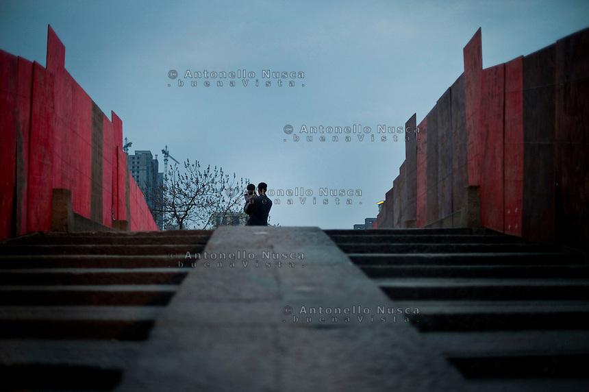 Un uomo con in braccio il proprio figlio sul vecchio ponte di Hangzhou.<br /> A man with his son stand in the middle of the old bridge in Hangzhou
