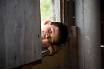 Belizean boy in the window of his home near Punta Gorda, Belize