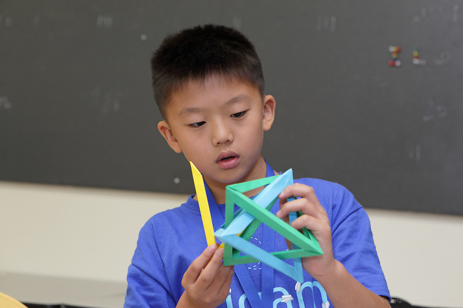 Phillip Jones teaches Tom Hull's Five Intersecting Tetrahedra to a class at the OrigamiUSA 2014 convention. Joey Cho concentrates on assembling his model.