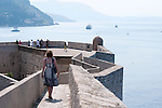 Walking on the city walls in Dubrovnik, Croatia with a view of the sea and the mountains in the background.