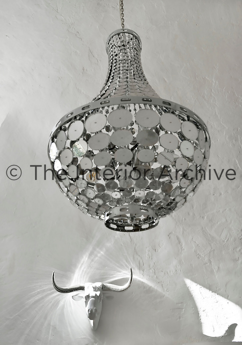 A retro chandelier reflects an interesting light on the plaster sculpture of a bull's head
