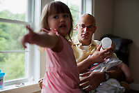 Fred Bermont holds daughter Elyse Bermont (age 2.5, left) and son Dylan Bermon (age 9 months) in their home in Lexington, Massachusetts, USA, before he goes to work and drops the kids off at day-care on June 9, 2014. Bermont is the father of two children and shares parenting duties with his wife, Jen Bermont. Fred usually takes care of the morning routine, including feeding, dressing, and dropping the kids off at day-care, and Jen picks them up and watches over them in the afternoon. Fred is a Senior Clinical Standards Specialist at Shire, a pharmaceutical company with headquarters in Lexington.
