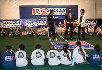US Soccer Foundation President and CEO Ed Foster-Simeon talks with a group of local children along with First Lady Michelle Obama and DC United player Jaime Moreno during a US Soccer Foundation clinic held at City Center in Washington, DC.