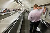 A man descends an escalator on the London underground.