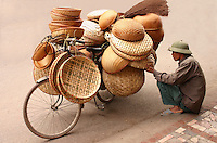 Baskets Vendor,  Hanoi Old Quarter - One of the most endearing sights of Hanoi is that of its ubiquitous vendors peddling baskets, fruit or baguettes through the streets according to their local beat.  Whether sold from the back of a bicycle or baskets balanced on bamboo shoulder poles, street vendors are very much a part of the Hanoi scene.