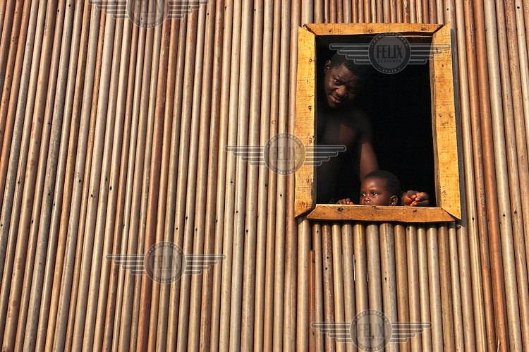 A man and his son look through the window of their bamboo house built on stilts above the water.