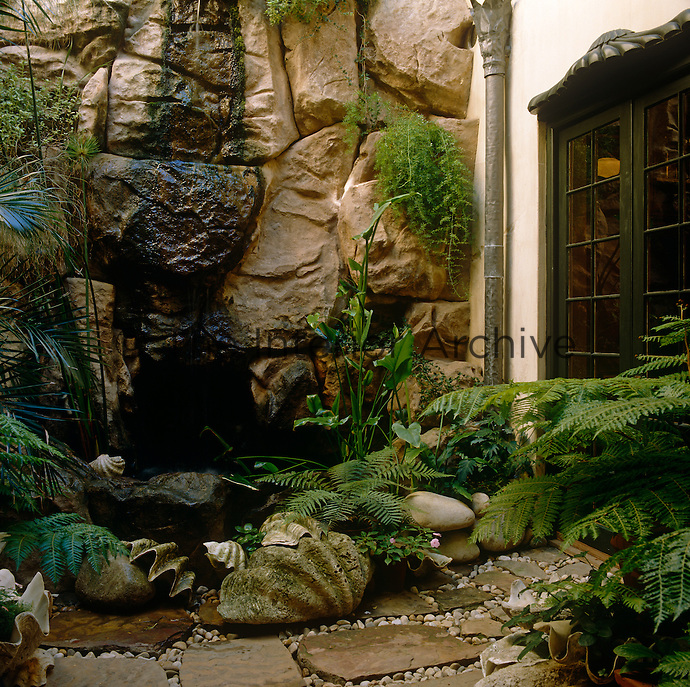 The patio of a house in South Africa has been built to take advantage of a natural rocky outcrop and waterfall