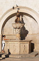 The small fountain of Onofrio, mala Onofijeva fontana, on the loggia loge Luza central square. A woman in white standing by the fountain. Doves. Dubrovnik, old city. Dalmatian Coast, Croatia, Europe.
