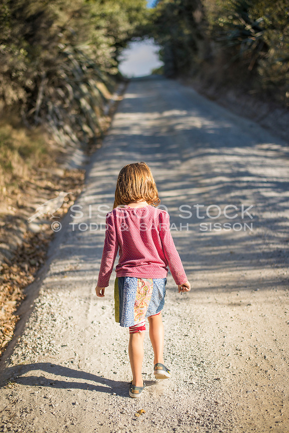Young girl walking up a gravel road in the late afternoon, New Zealand - stock photo, canvas, fine art print