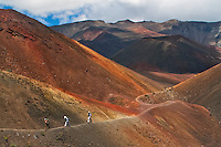 Three male hikers along the colorful orange hues lava trail at Pele's Paint Pot in the crater of HALEAKALA NATIONAL PARK on Maui in Hawaii USA