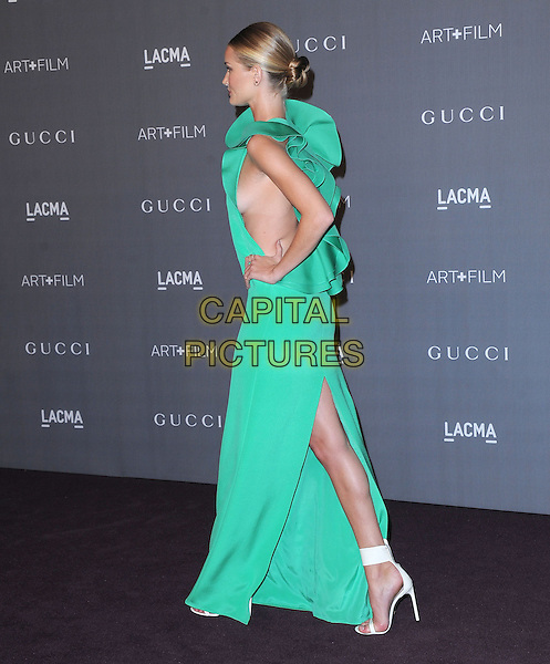 Rosie Huntington-Whiteley.at The LACMA 2012 Art and Film Gala held at LACMA in Los Angeles, California, USA, October 27th 2012..full length dress green sleeveless high neck folded long maxi silver clutch bag hand on hip walking boob walking slit split side .CAP/RKE/DVS.©DVS/RockinExposures/Capital Pictures.