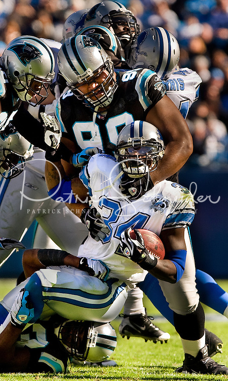 Detroit Lions running back Kevin Smith (34) is tackled by Carolina Panthers defensive tackle Maake Kemoeatu (99) during an NFL football game at Bank of America Stadium in Charlotte, NC.