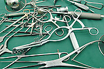 A pile of stainless steel surgical instruments, including a range of forceps, surgical retractors, towel clips, scissors, a bone nibbler, a curette, and a surgical bone hammer. The instruments are clean but not sterile. Royalty Free