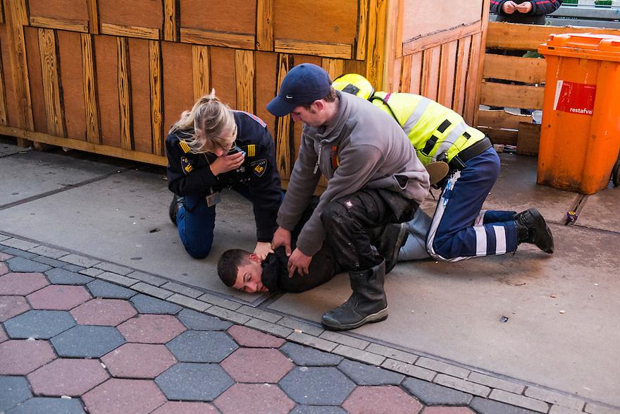 Nederland, Amsterdam, 11 jan 2014<br /> Op het Damrak wordt een verdachte gearresteerd door de politie.  <br /> Foto: Michiel Wijnbergh