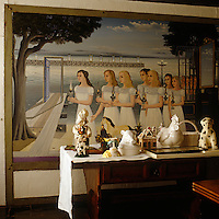 A painting by Paul Delvaux titled 'The Intelligent Virgins' is mounted within the wall of the dining room behind a display of ceramic sculptures on a side table