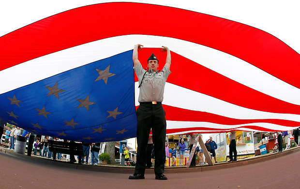 Alexander Lesher of West Des Moines, a member of the Central Campus JROTC, holds up the center of a 20x36 foot American Flag during the veteran's day parade Monday at the Iowa State fair.  Veterans and Active duty military were honored during the parade.   (Christopher Gannon/The Register)  --  des.m0814fair - shot by Christopher Gannon/The Register on 8/13/12 in Des Moines, IA