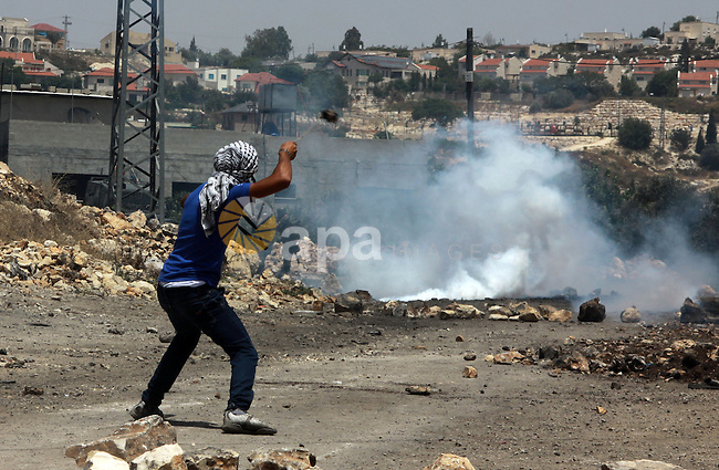 A Palestinian protester throws stones towards Israeli security forces during clashes following a weekly protest against the expropriation of Palestinian land by Israel in the West Bank village of Kfar Qaddum, near Nablus on June 20, 2014. Photo by Nedal Eshtayah
