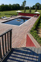 The swimming pool is situated behind the house surrounded by a large wooden sun deck