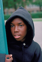 African American teen age 12 standing by a street sign wearing a hooded sweat shirt.  St Paul Minnesota USA