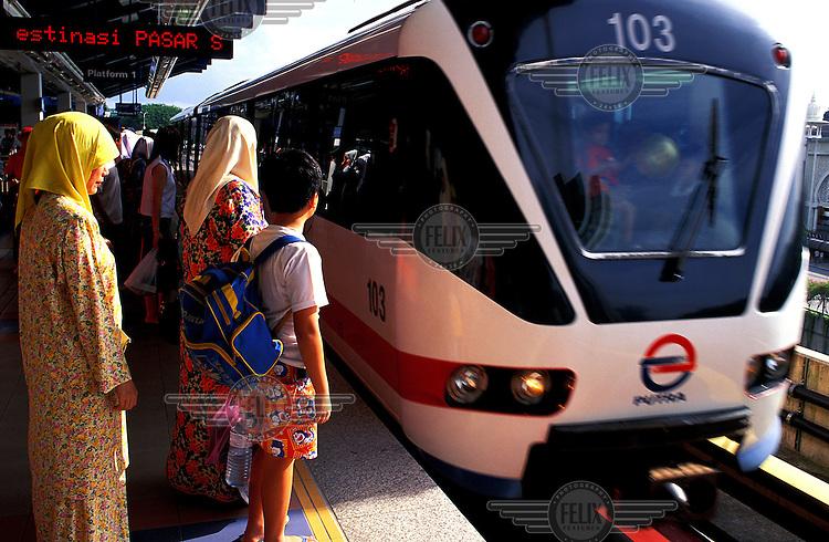 Local passengers wait to take the new over-head railway in Kuala Lumpur, Malaysia's capital city.  Credit: Chris Stowers.