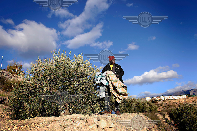 An illegal migrant, from Sub-Saharan Africa, looks for a place to sleep at an olive farm. Many of migrants come to the region to pick olives but this year there is competition for the work. The economic collapse means that work once shunned by the indigenous population is now sought after by unemployed Spaniards.
