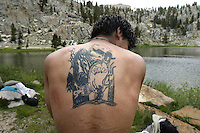 "Jonathan Gallardo,(cq) 16,  paid $140 to have image of a grim reaper and tombstone tattooed on his back. ""I'm going to have my name tattooed on that tombstone when I turn 18,"" . says Gallardo as he enjoys an afternoon swim after a long days hiking in Sierras Golden Trout Wilderness. Profile of Outward Bound Adventures, a nonprofit organization that introduces at-risk urban teens to the therapeutic benefits of time spent in the wilds, there motto is; ""Share the Earth, Challenge a Child"". Known as OBA, the group brought 12 teens, all continuation high school students from the Pico Union and Watts areas of downtown Los Angeles on a 28-mile trek July 31 - August 9, 2005. OBA annually brings Los Angeles teens into the High Sierra's."