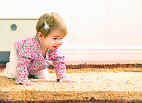 Toddler girl with white bow in her hair learning how to crawl.
