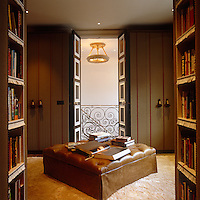 A leather ottoman occupies the centre of this library cum dressing room