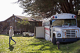 USA, California, Big Sur, Esalen, woman walks by an old school bus in front of the Farm House at the Esalen Institute