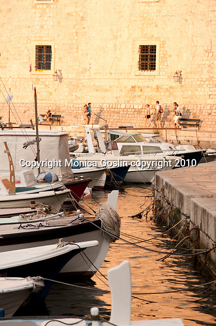 Boats tied up at the port in Dubrovnik, Croatia at sunset.