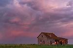 Sunset lit storm clouds over an abandoned house near Val Marie, Saskatchewan.