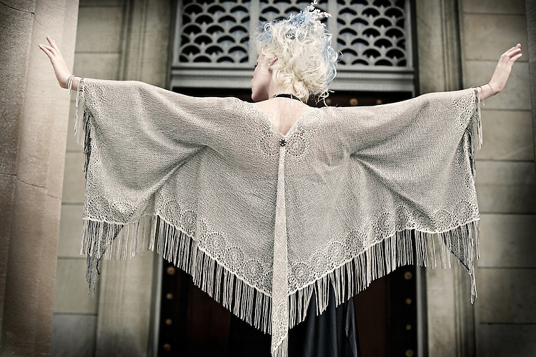 The back of a woman with blonde and blue hair wearing a shawl spreads her arms out like she's trying to fly