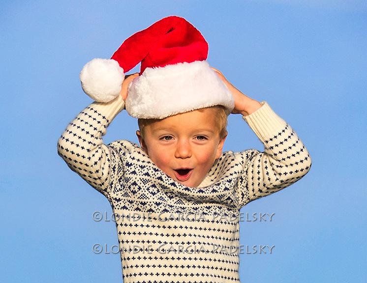 Little boy wearing Santa hat!