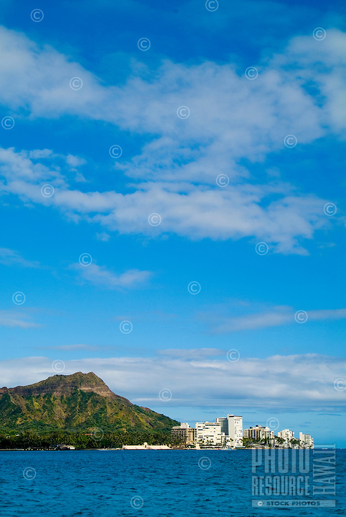 The tip of Diamond Head fronted with a cluster of small hotels and condos with beautiful blue water in the foreground.