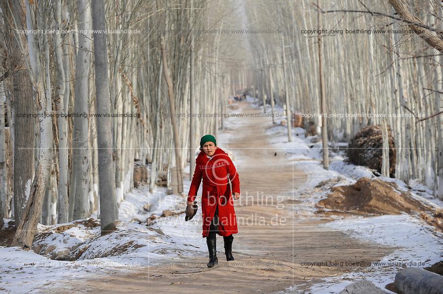 CHINA province Xinjiang, uighur town Opal near Kashgar, woman in red coat walking along poplar tree avenue / CHINA Provinz Xinjiang, uigurische Stadt Opal bei Kashgar, hier lebt das Turkvolk der Uiguren, das sich zum Islam bekennt