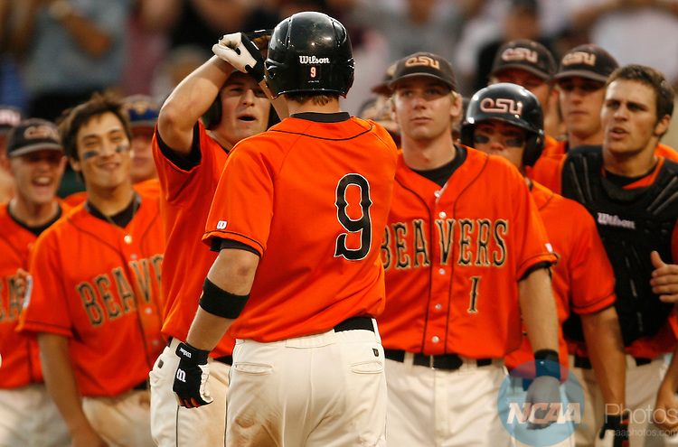 24 JUNE 2006:  John Wallace (35) of Oregon State University congratulates teammate Cole Gillespie (9) after his 2-run homerun against Andrew Miller (33) of the University of North Carolina during the Division I Men's Baseball Championship held at Rosenblatt Stadium in Omaha, NE.  Jamie Schwaberow/NCAA Photos