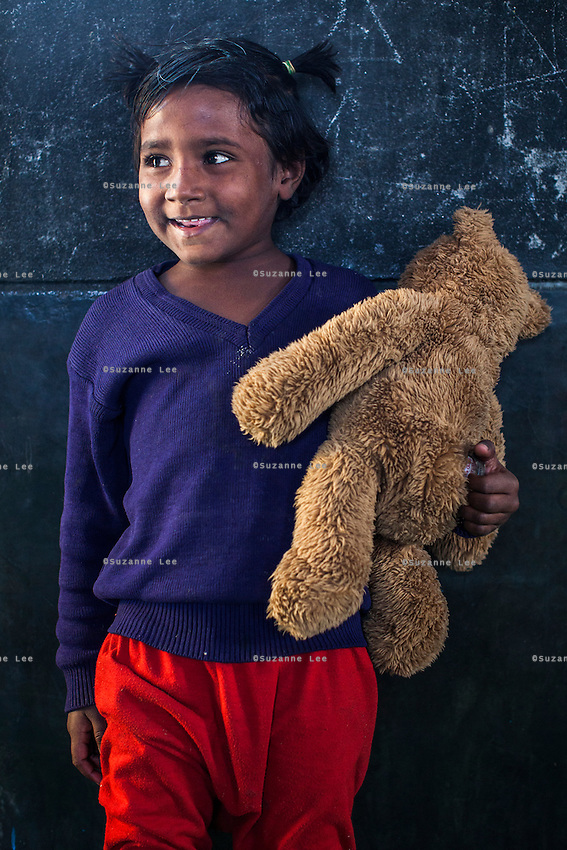 Shabnam, 3, poses for a portrait with a soft toy in the Guria Non-Formal Education center in the middle of the Shivdaspur red light district, Varanasi, Uttar Pradesh, India on 20 November 2013. Guria uses the soft toys as a form of therapy for the children of the women in prostitution and also use it as signals of the children's emotional wellbeing.