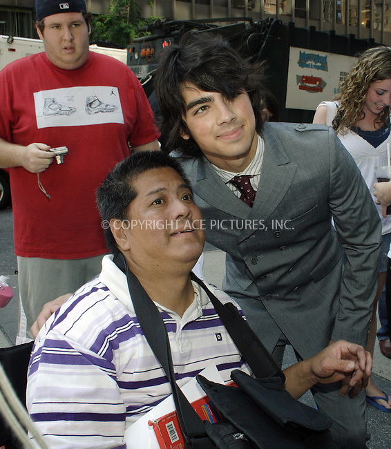 WWW.ACEPIXS.COM . . . . .  ....August 9, 2007. New York City.....**EXCLUSIVE**....Joe Jonas of the Jonas Brothers poses with a fan outside the CW11 Studios in New York City.....Please byline: Joanne Juele - ACEPIXS.COM.... *** ***..Ace Pictures, Inc:  ..Philip Vaughan (646) 769 0430..e-mail: info@acepixs.com..web: http://www.acepixs.com