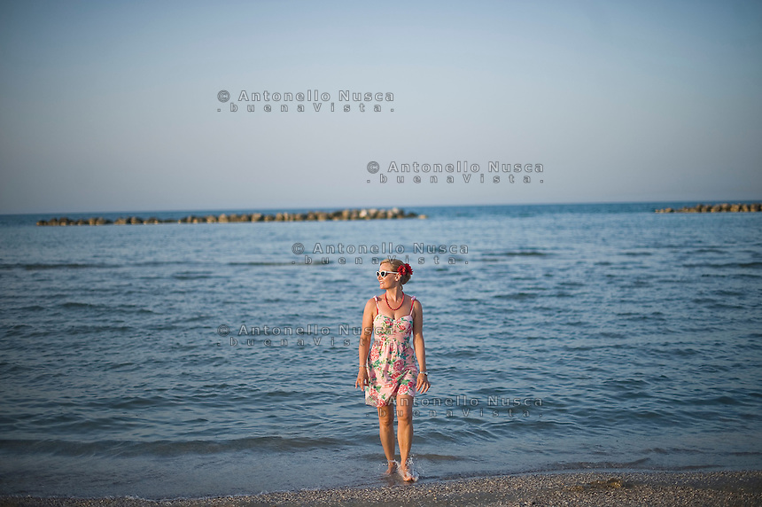 Senigallia, Agosto 2013. Una ragazza vestita da pin-up in una spiaggia di Senigallia durante il Festival Summer Jamboree.