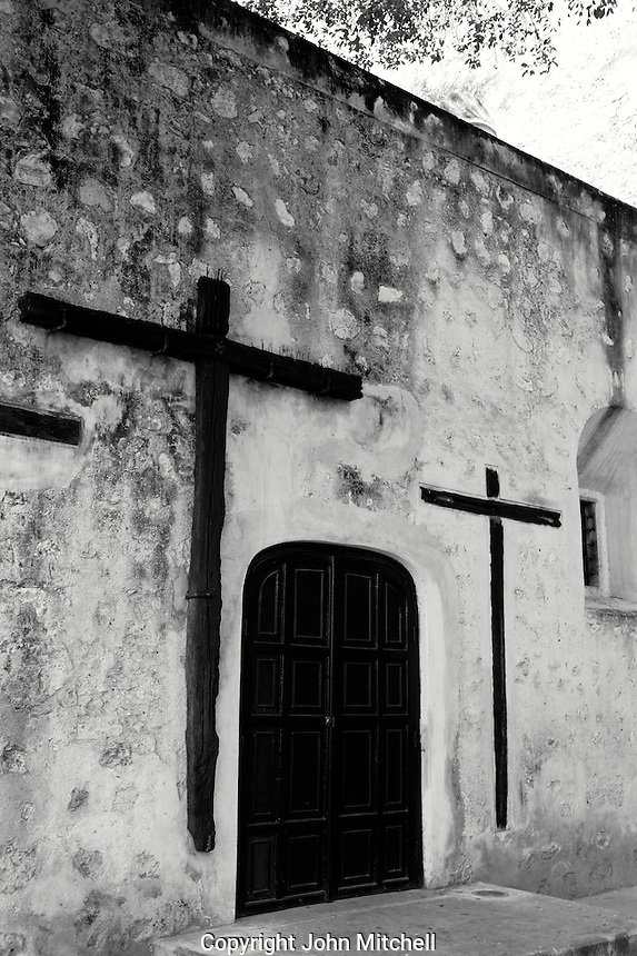 Side door and crucifixes of the 16th century cathedral or Catedral de Ildefonso on Plaza Grande in Merida, Yucatan, Mexico..