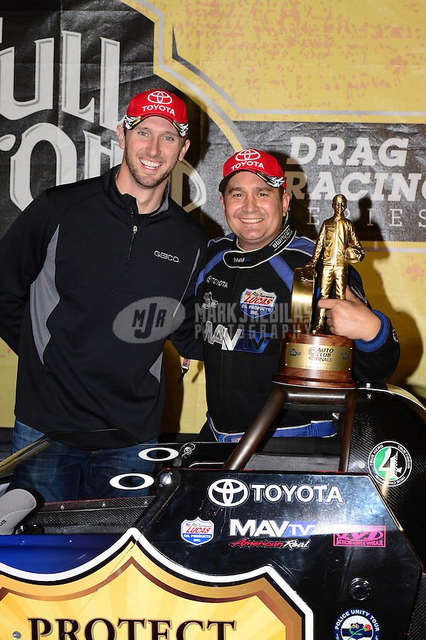 Nov. 11, 2012; Pomona, CA, USA: NHRA top fuel dragster driver Brandon Bernstein (right) celebrates with teammate Morgan Lucas after winning the Auto Club Finals at at Auto Club Raceway at Pomona. Mandatory Credit: Mark J. Rebilas-