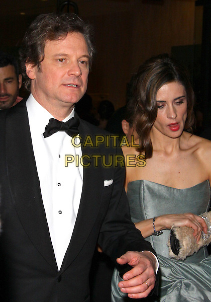 COLIN FIRTH & LIVIA GIUGGIOLI .Golden Globe Awards - departures  at The Beverly Hilton Hotel,  Los Angeles, CA, USA, 16th January  2011..half length tuxedo bow tie black white shirt strapless green gray gray couple husband wife .CAP/ADM/TC.©T. Conrad/AdMedia/Capital Pictures.