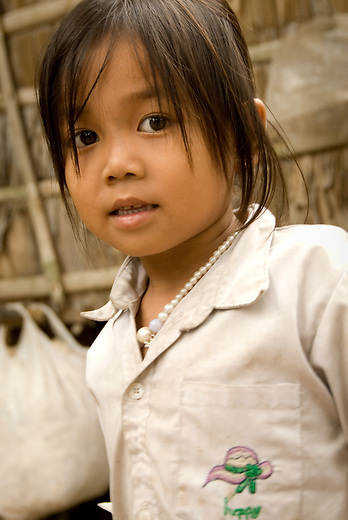 A young Cambodian girl proudly displaying her English clothing and pearls. Many clothes are donated or sold through second hand markets.