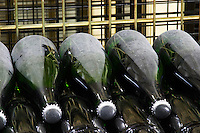 Wine Bottles of champagne resting horizontally on the side undergoing secondary fermentation stacked in wire cages and closed with crown caps (capsules) at Champagne Deutz in Ay, Vallee de la Marne, Champagne, Marne, Ardennes, France